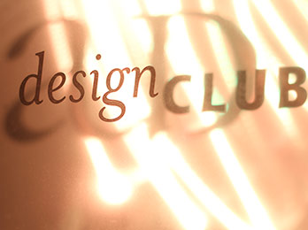 Photo of Design Club text, AU Design logo, and bright golden lights in the background